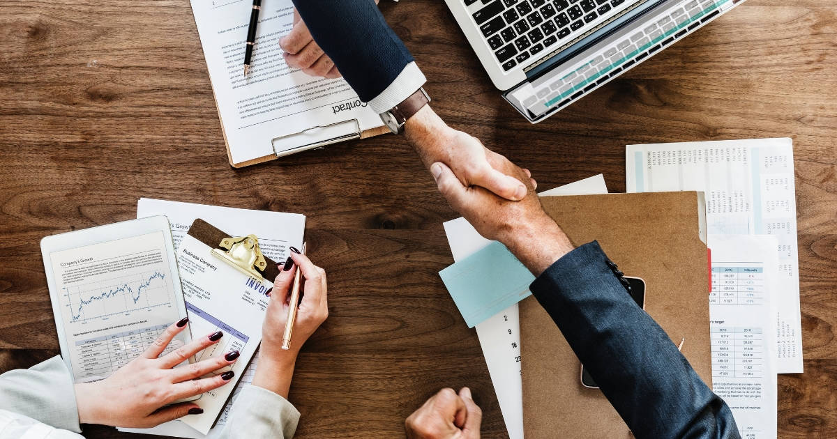 fiduciary shaking hands with couple after reviewing their finances