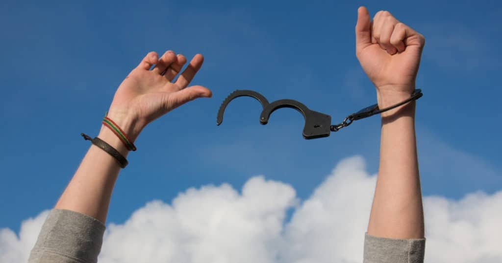 hands raised with handcuffs coming off as symbol of breaking the debt cycle