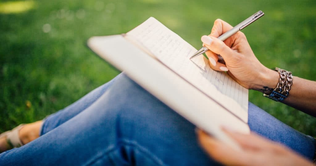 woman sitting on the grass writing a letter