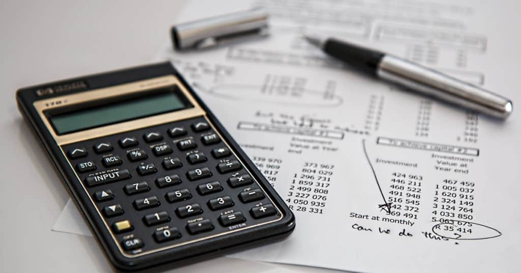 black calculator on desk with budget and pen to set financial goals