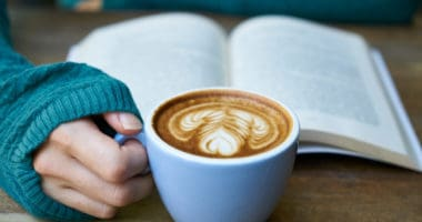 woman reading Rich Dad Poor Dad Book with coffee in hand