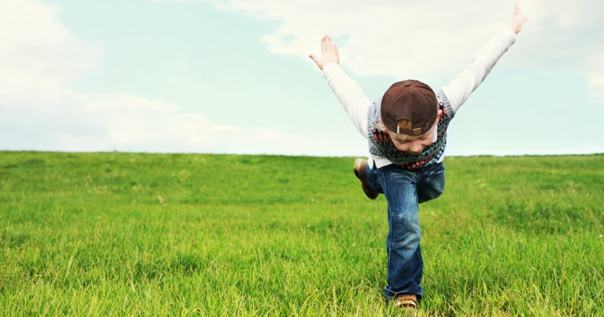 young boy playing in grass after using famzoo