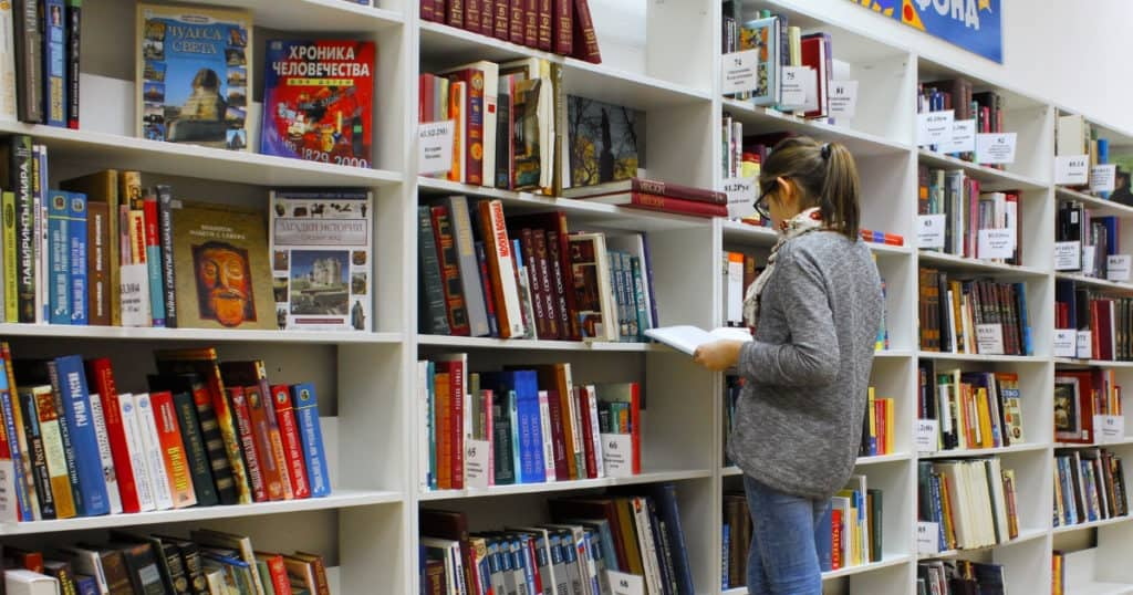 girl standing in college library looking at books