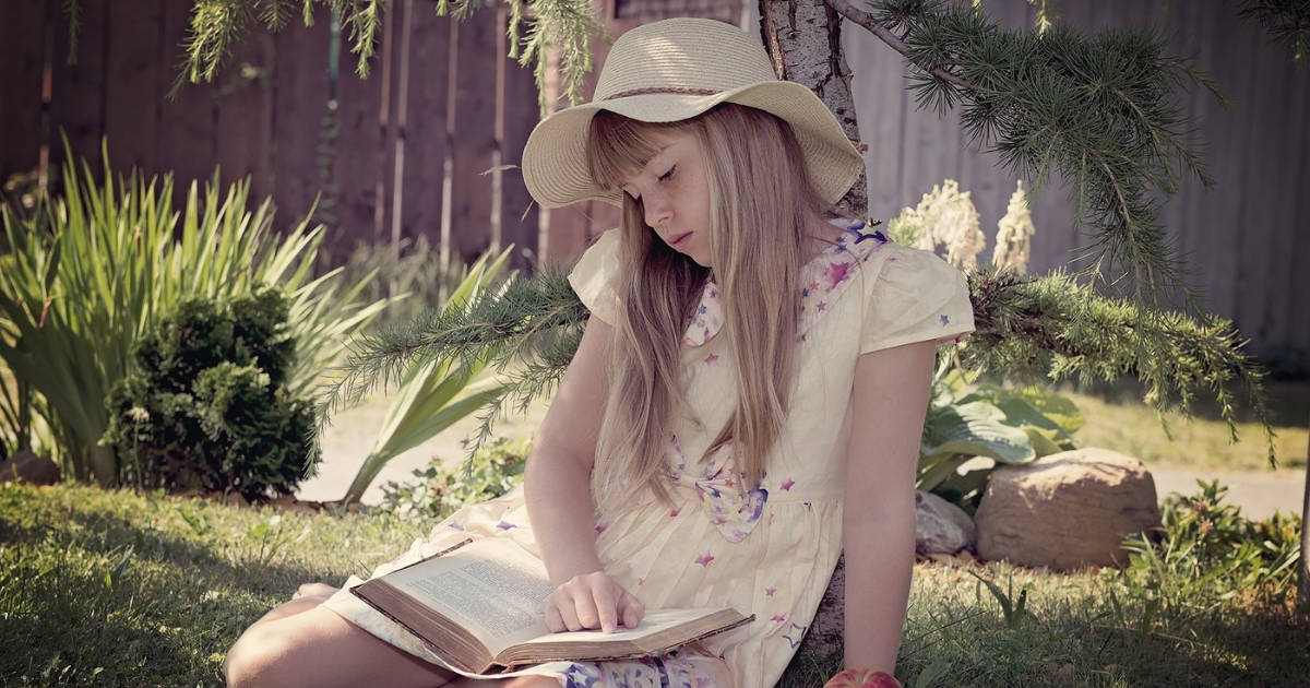 middle school girl sitting outside reading a money book