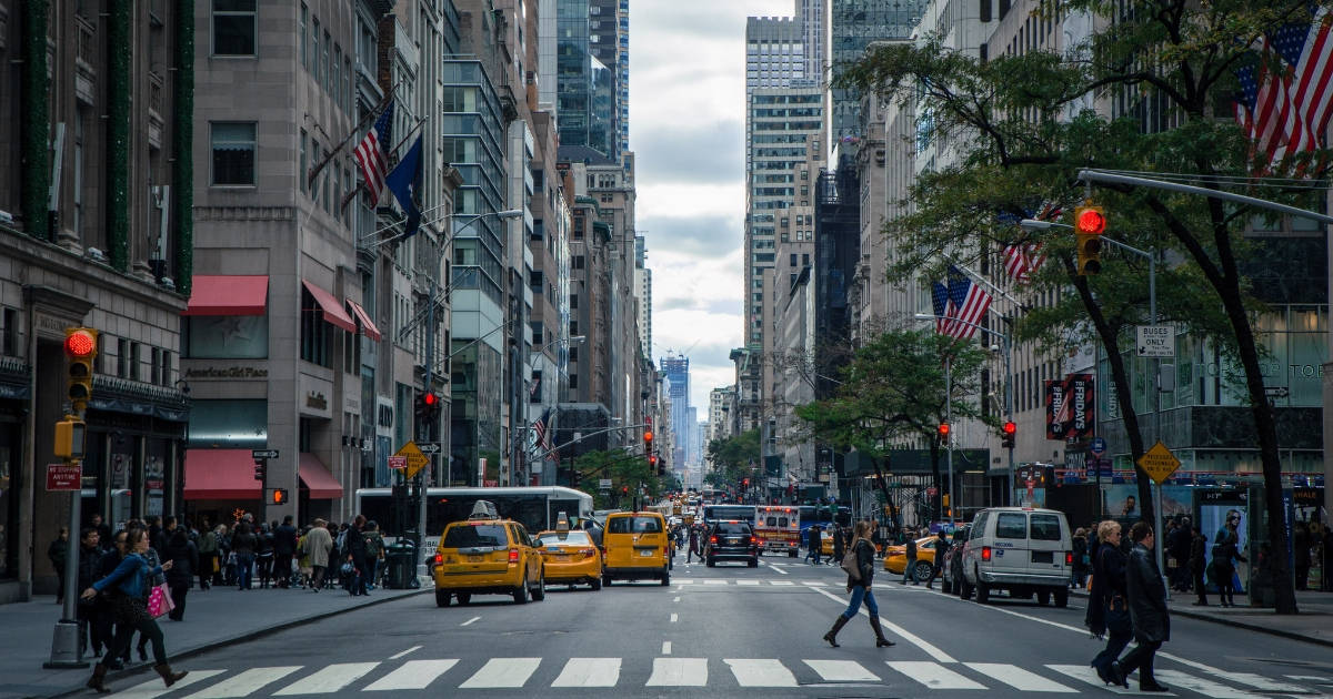 city streets of New York with taxis and people walking