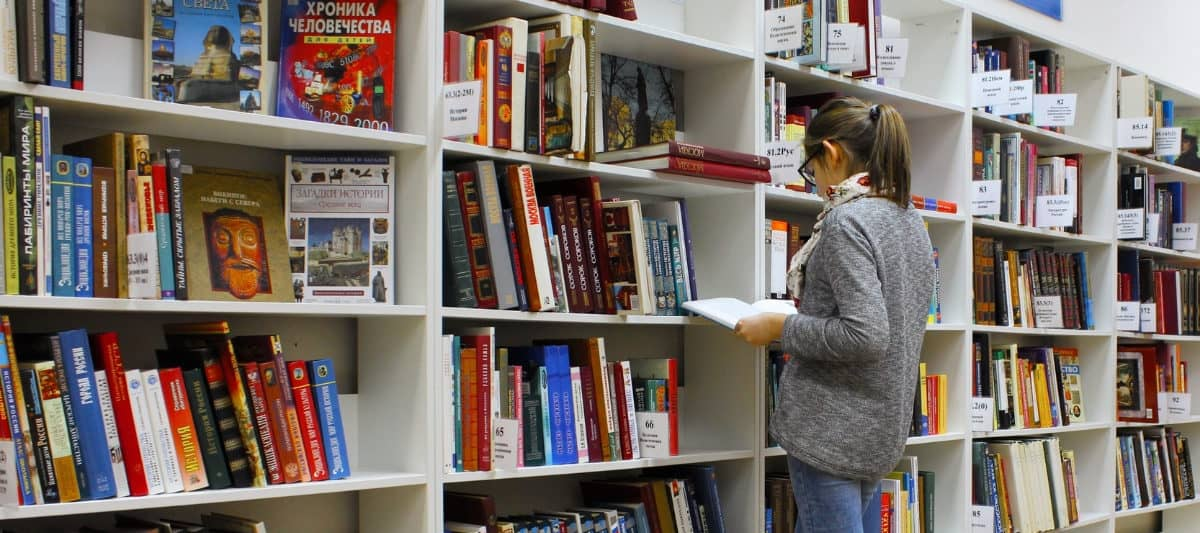 young girl in college library looking at books