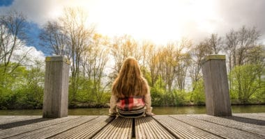 woman sitting on dock overlooking lake contemplating Roth or Traditional IRA