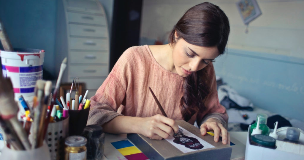 woman painting picture to sell on Etsy