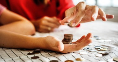 couples hands with coins talking about investing in peak markets