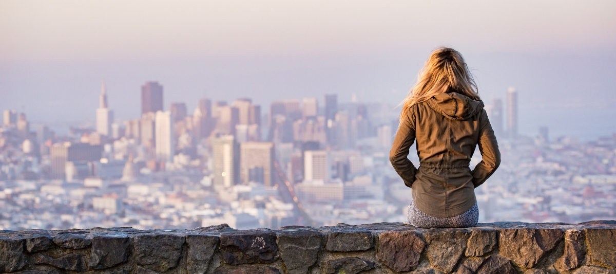 woman sitting on stone wall overlooking city after her financial awakening