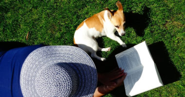 woman laying in grass with dog reading a book from her personal finance summer reading list