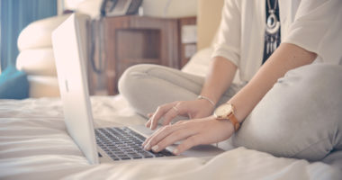 woman sitting on her bed with laptop working from home