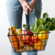 woman holding grocery basket full of produce