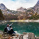couple sitting by lake in the mountains on a summer date