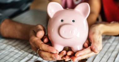 family holding piggy bank as a way to teach your preschooler about money