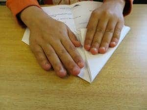 Child folding paper airplane
