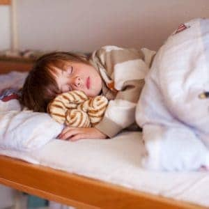 Little boy sleeping on bunk bed