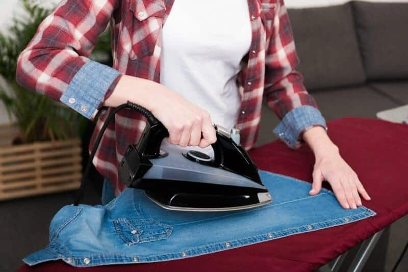 Woman ironing a jean shirt