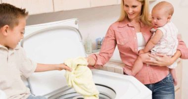 Woman doing laundry with her children