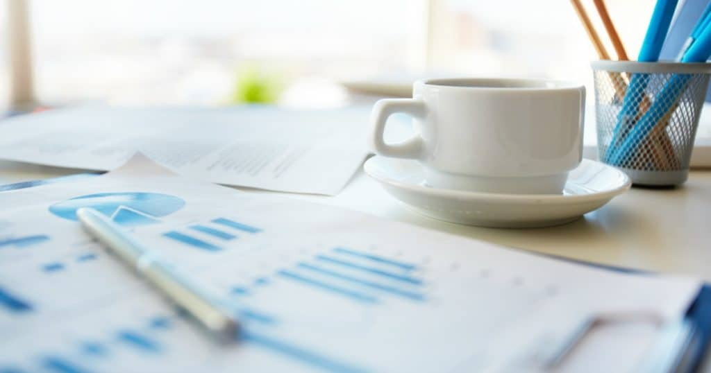 Paperwork on desk with coffee cup considering types of annuities