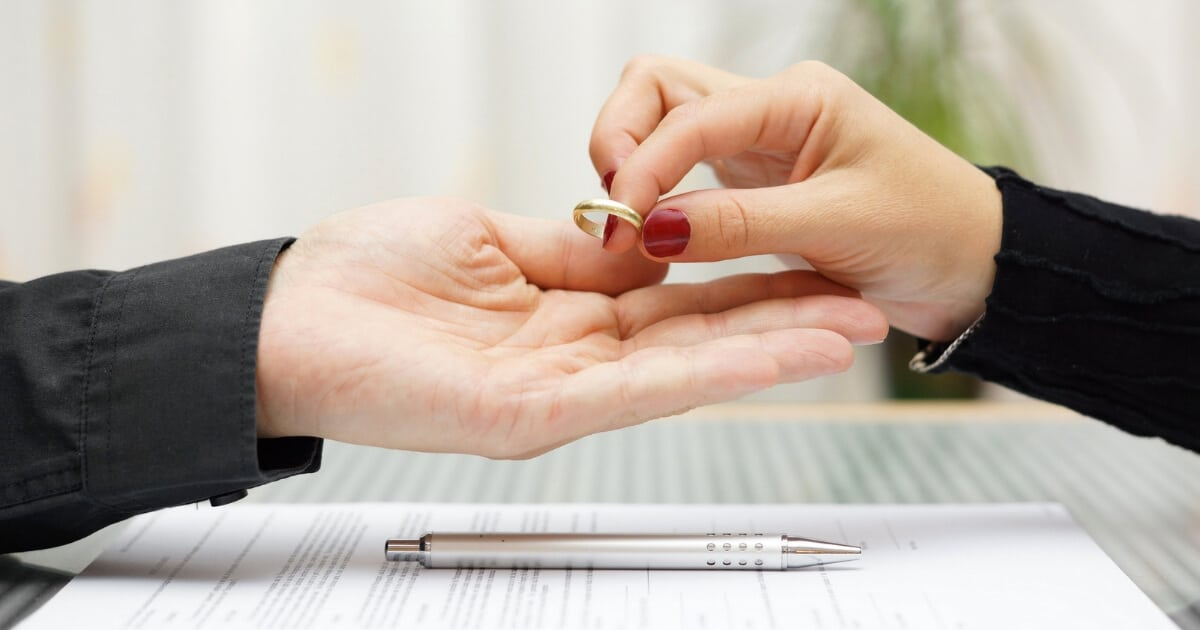woman handing ring back to man after divorce