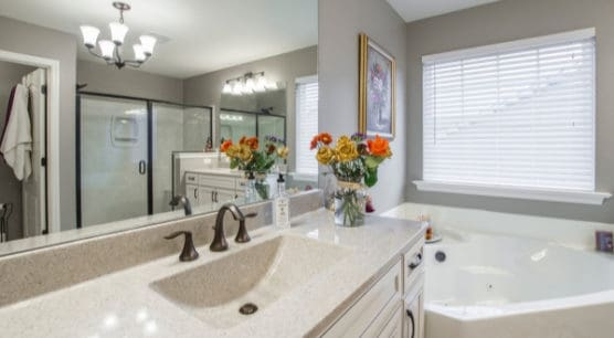clean white bathroom with flowers on vanity