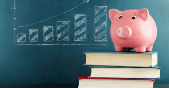 Piggy bank on books with blackboard - Should you refinance your student loans?