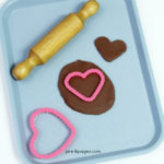 Valentine's Crafts Chocolate Playdough Hearts on pan with cookie cutter