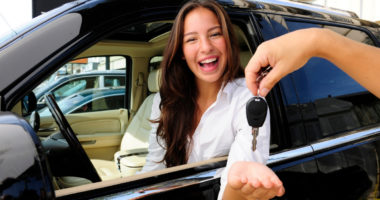 woman who bought a car is excited to be receiving the keys for the first time