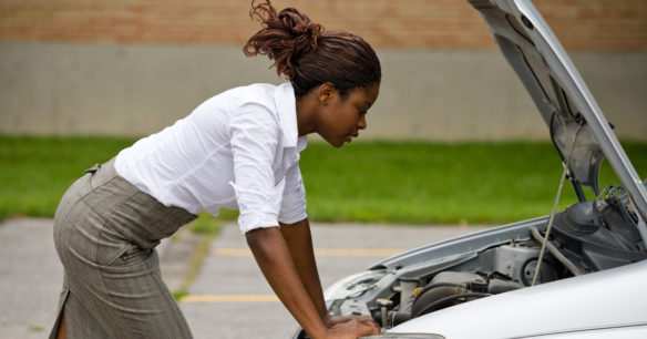 woman standing over broken down car departing whether to buy a car or fix hers