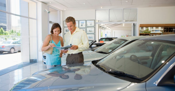 couple buying a car from a dealership showroom