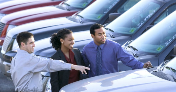 couple wanting to buy a car looking at vehicles with a salesman on a car lot
