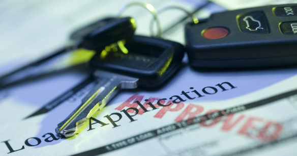 keys sitting on loan application to buy a car