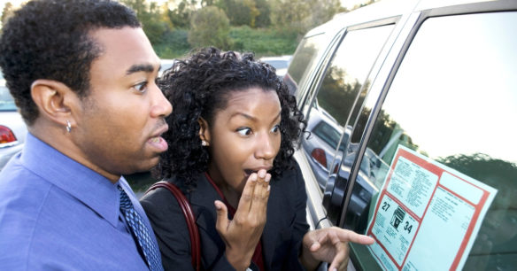 couple looking at price tag of car they are interested in buying