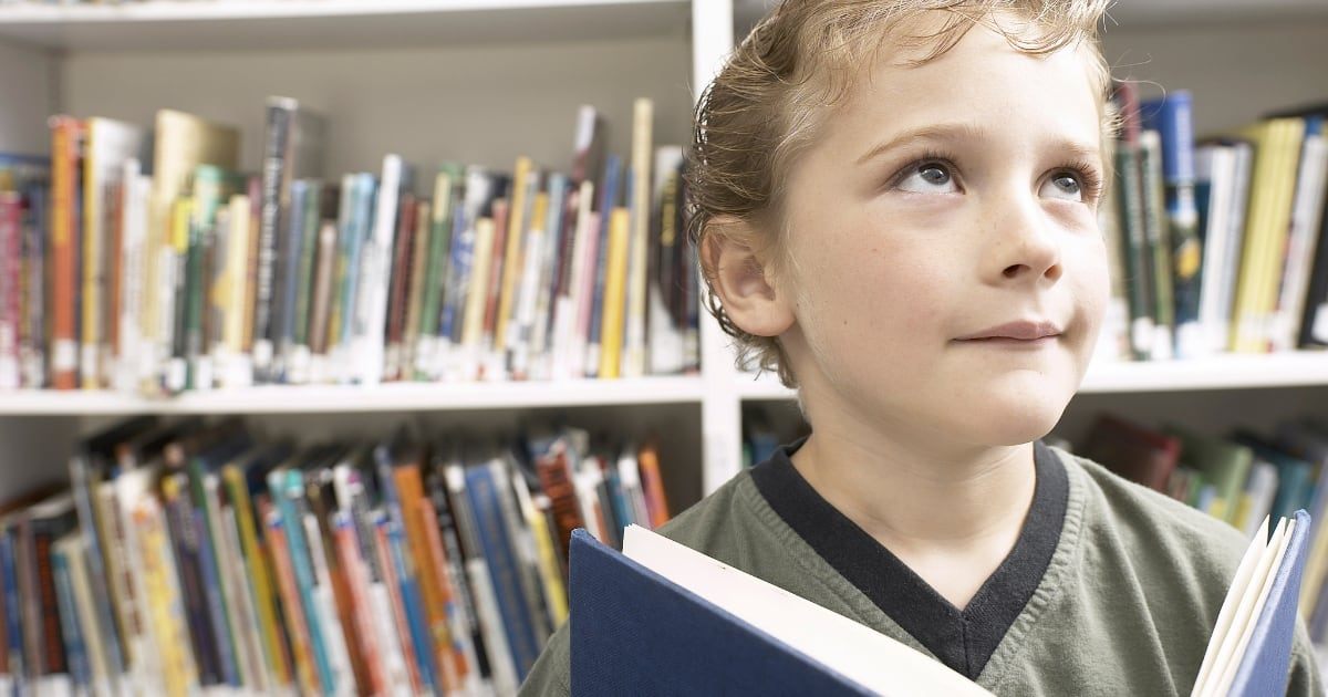 Blonde young boy with an open book in front of library shelves