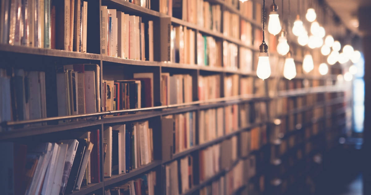 Shelves of books in a library with hanging rustic lights above