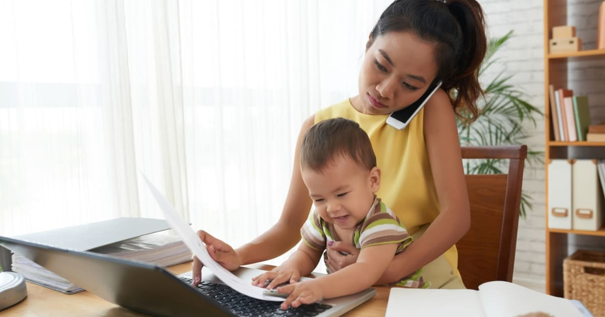 mom returning to work after maternity leave working on phone and computer with baby in lap