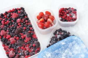 Frozen berries in plastic containers in snow