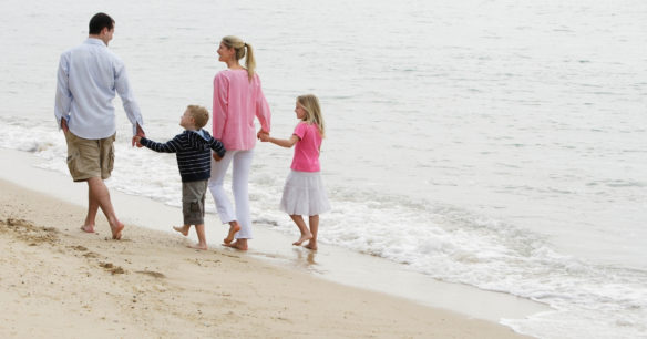 a family who has it all walking together hand in hand on the beach / mom, dad, little boy and little girl