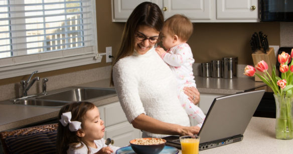 woman multitasking on computer holding a baby and feeding a toddler