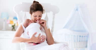 new mom with newborn in nursery