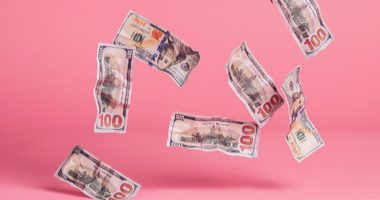 Money falling from above, pink background