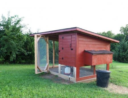 Red backyard chicken coop with run door open